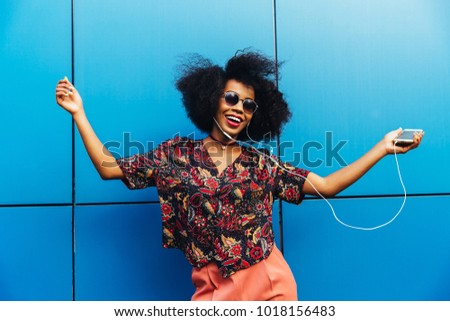 Charming amazing afro american young woman in sunglasses, dancing while listening to music in headphones on her mobile phone. Dressed in colorful blouse. Fun time outdoors.