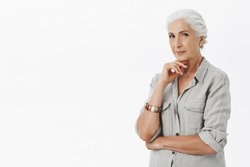 Charming and creative smart senior woman creating new ideas for future business not want retire holding hand on chin in thoughtful pose smiling with delight having idea, thinking over gray background