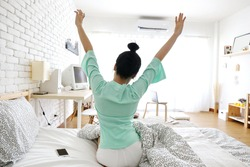 Charming Asian woman sit on bed and hand up wake up on morning in simple white room with air condition. summer season.