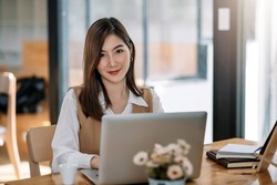 Charming Asian woman working at the office using a laptop Looking at the camera.