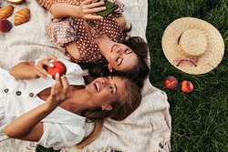 Charming attractive blonde and brunette girls in summer dresses lay on linen rug and have picnic. Cool woman in polka dot dress holds phone.