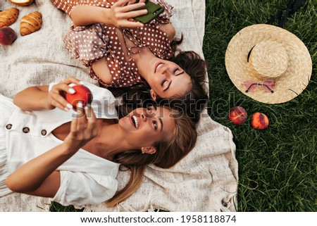 Charming attractive blonde and brunette girls in summer dresses lay on linen rug and have picnic. Cool woman in polka dot dress holds phone. Сток-фото ©