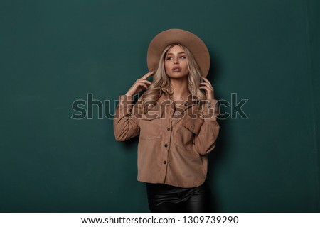 Charming attractive young woman in a stylish elegant beige hat in a trendy shirt in vintage black leather pants with blond curly blond hair stands indoors near the green wall. Modern beautiful girl. #1309739290