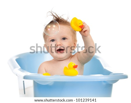 charming baby having bath in blue tub and playing with soap bubble