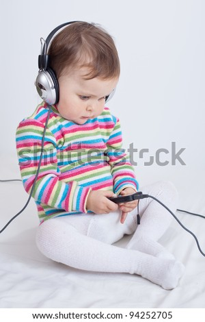 Charming baby in headphones listens music by telephone. Studio shot