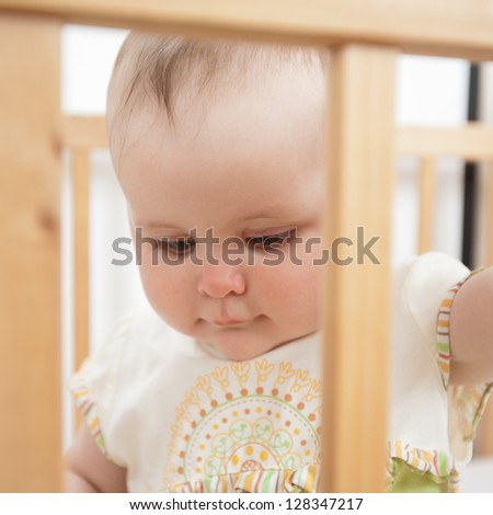 Charming baby indoor. Baby girl in child bed