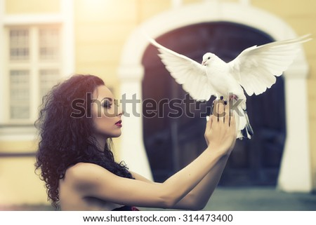 Charming beautiful delicate young woman with bright make-up with long curly brown hair in profile holding a white pigeon in her hands on blur building background outdoor, horizontal picture