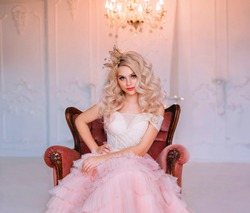 Charming beautiful delightful young girl princess sitting in antique vintage armchair waiting fairy miracle. Queen woman smiles mysteriously cute. Blonde long curly hair. Delicate pink airy sexy dress