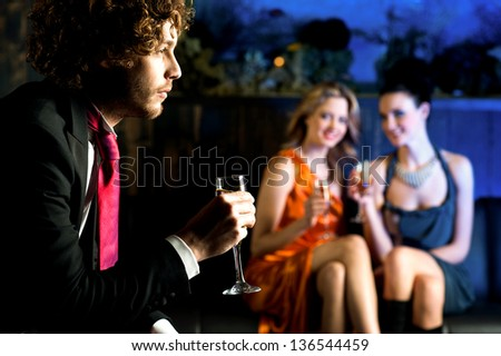 Charming beautiful girls looking at handsome young guy in a bar.