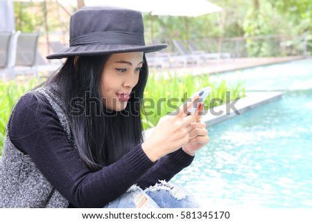 Photo of Charming beautiful tan skin Asian business chic woman hand work on laptop phone and write pen on notebook dairy sit on chair side of swimming pool. Presenting your product with good looking woman.