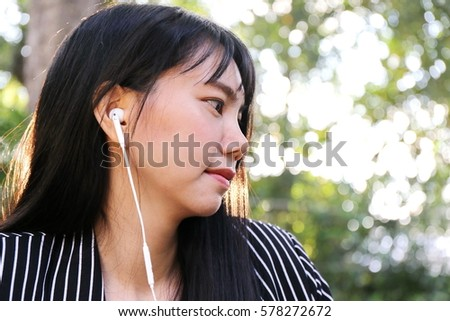 Photo of Charming beautiful tan skin Asian business chic woman listen song with earphone in sunset light in forest with good relaxing smile emotion. Presenting your product