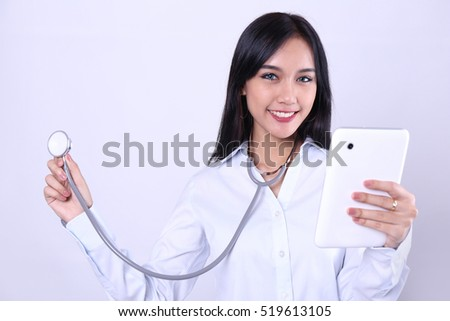 Charming beautiful tan skin Asian woman doctor hand holds stethoscope. Presenting your product. An enthusiastic intern looking at camera with confidence and hand hold tablet.