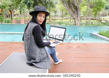 Photo of Charming beautiful tan skin Asian woman hand use phone and laptop side swimming pool . Presenting your product with good looking chic business woman. copy space.