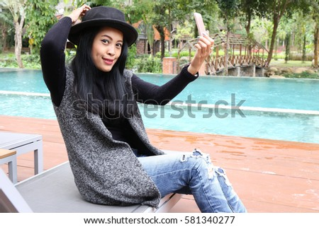 Photo of Charming beautiful tan skin Asian woman hand use phone and laptop side swimming pool . Presenting your product with good looking chic business woman.