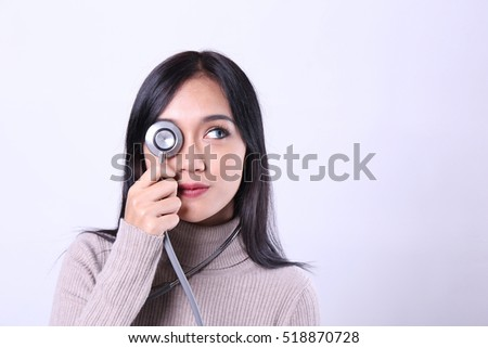 Charming beautiful tan skin smart Asian woman doctor hand holds stethoscope. Presenting your product. An enthusiastic intern looking at camera with confidence and smiling.