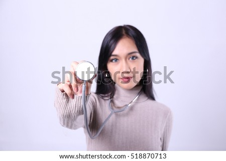 Charming beautiful tan skin smart Asian woman doctor hands hold stethoscope. Presenting your product. An enthusiastic intern looking at camera with confidence and smiling.