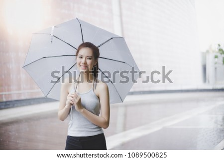 Charming beautiful young woman. Attractive beautiful lady hold an umbrella. It's rainy day. Lovely girl is walking at city when light rain. It's rainy season. She look so relaxed and happy. copy space