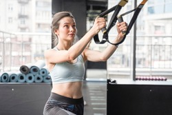 Charming beauty caucasian girl learning hard workout with total body resistance exercise TRX for training pull and look up. Sport conception