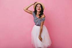 Charming black-haired girl in romantic outfit posing on pink background. Studio shot of wonderful lady in lush skirt enjoying photoshoot.