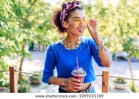 Charming  black woman with stylish  African hairstyle with headband spending her weekend in the park, walking and drinking lemonade.