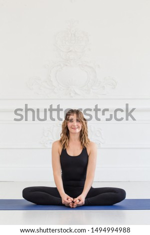Charming blond woman in sport outfit sits on carpet and touches her feets with her hands