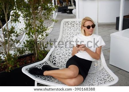 Charming blonde female is looking away, while is sitting in comfortable chair with mobile phone in hands. Hipster girl in fashionable clothes is using cell telephone during rest in modern coffee shop