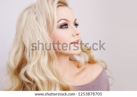 Charming blonde with luxurious blonde curls. Hair beauty and health #1253878705