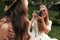 Charming blonde woman in stylish white dress and red sunglasses smiles and takes photo of her friend. Tanned girl holds retro camera. Brunette lady in boater has picnic. Blurred effect.