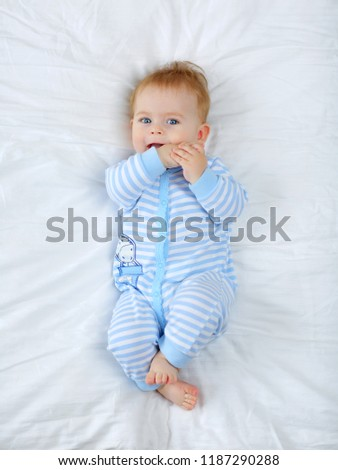 Charming blue-eyed baby 7 month old lying in bed in a striped bodysuit