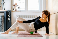 Charming brunette woman using trigger point massage ball doing self-massage technique applying for back and pelvis pain relief , working out on fitness mat at floor at home interior on background.