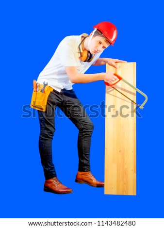 Charming brutal worker works with a hacksaw and board. Blue background.