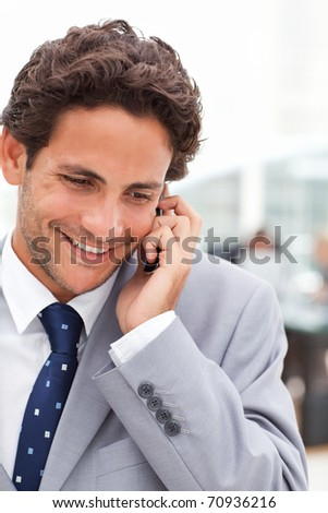 Charming businessman phoning in his office