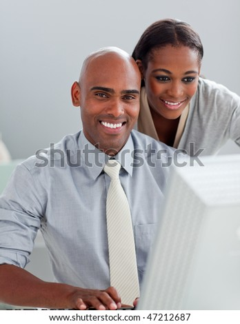 Charming businesswoman helping her colleague at a computer in the office