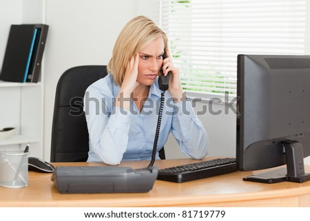 Charming  businesswoman on phone looking at screen while having headache in her office