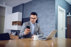 Charming caucasian bearded businessman with eyeglasses and in suit sitting at home and using smart phone. On table is laptop and mug with fresh morning coffee.