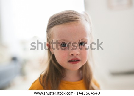 Charming Caucasian girl child blonde 4 years old with Down syndrome in a yellow T-shirt, close-up portrait, bright interior