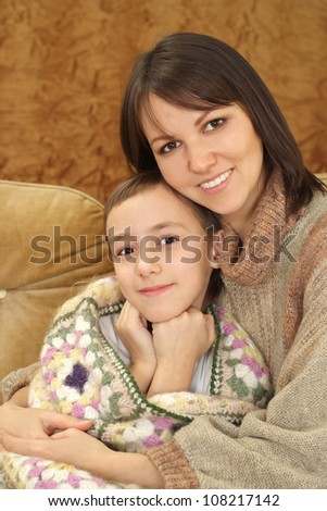 Charming Caucasian mama with her son on a brown background
