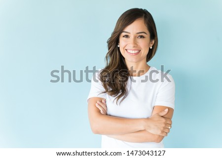 Charming Caucasian woman with arms crossed smiling against colored background