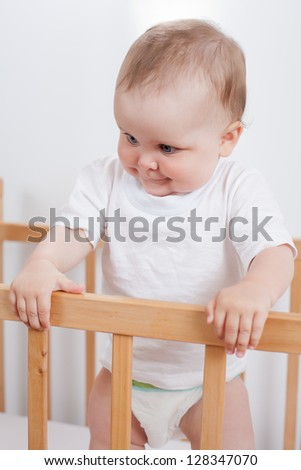 Charming child in the crib.  Charming baby stands in child bed and looking down