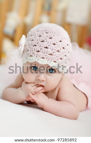 Stock Photo Charming child. Little girl with hat lying on her stomach and sucks fingers