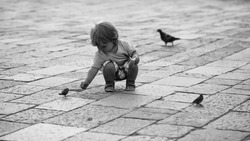 Charming child. Photo closeup of cute fair-haired blond kid tiny little child baby boy feeding birds with bun sitting on haunches on flag-stone pavement cityscape on blurred grey background