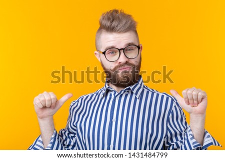Charming confident young fashion hipster man with glasses and a beard shows on himself posing over a yellow background. Place for advertising. The concept of self-confidence and success. #1431484799