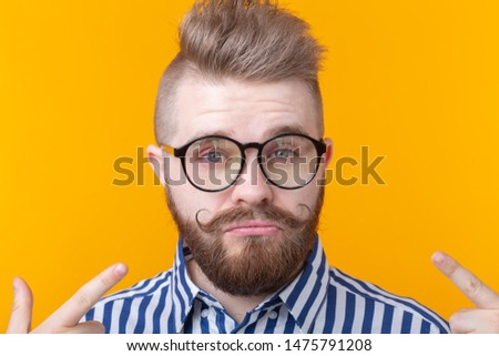 Charming confident young fashion hipster man with glasses and a beard shows on himself posing over a yellow background. Place for advertising. The concept of self-confidence and success. #1475791208