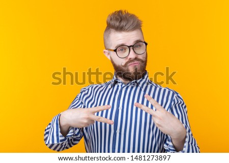 Charming confident young fashion hipster man with glasses and a beard shows victory gesture posing over a yellow background. The concept of self-confidence and funny. #1481273897