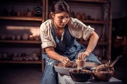 Charming craftsman enjoying pottery art and production process. Making ceramic dishes.