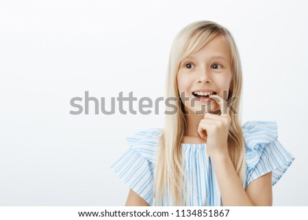 Charming creative young girl has great idea, deciding what to draw for mother birthday. Portrait of dreamy adorable child with blond hair, looking aside and biting finger with broad smile, imaging