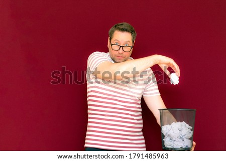 Charming curious caucasian man in stripet t shirt wears eye glasses hold recycling bin. this paper will go to bin with waste paper. save our planet. disposal of paper in trash mandatory quit