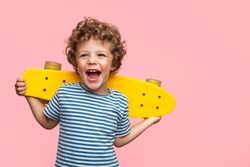 Charming curly boy holding yellow longboard and looking away on pink background.