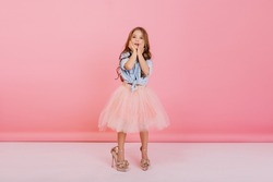 Charming cute little girl with long brunette hair in tulle skirt and blue shirt expressing isolated on pink background. Having fun in mother`s shoes of funny joyful child, cheerful mood