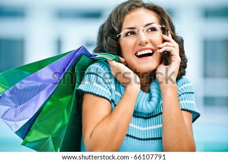 Charming dark-haired girl in beautiful glasses cheerfully laughs, talking by mobile phone against spacious hall. In hands she holds packages with purchases.